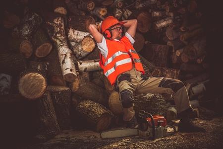 wood cutter: Lumber Wood Worker Break. Satisfied Lumber Worker Laying on the Pile of Wood Logs. Hard Work Satisfaction.