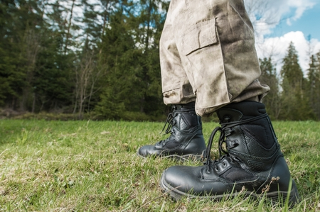 poacher: Poacher at Work Concept. Poacher Military Grade Shoes Closeup with Forest in the Background.