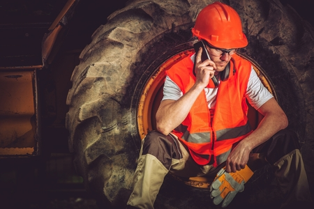 construction machinery: Hard Construction Business Concept with Caucasian Businessman Making Business Call While Seating Inside Heavy Duty Bulldozer Tire. Stock Photo