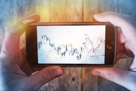 trader: Mobile Forex Trader. Financial Trading Application Concept. Trader Watching Forex Indexes on His Smartphone.