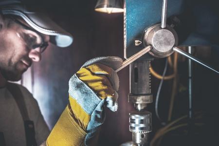 driller: Small Drill Works in a Garage. Caucasian Men Using Metal Driller Machine.