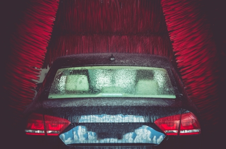 carwash: Automatic Brush Car Wash in Action. Elegant Modern Full Size Car in the Car Wash. Stock Photo
