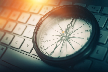 The Internet Navigator Concept Photo. Vintage Metallic Compass on the Computer Keyboard. Navigation Through the Internet. Foto de archivo