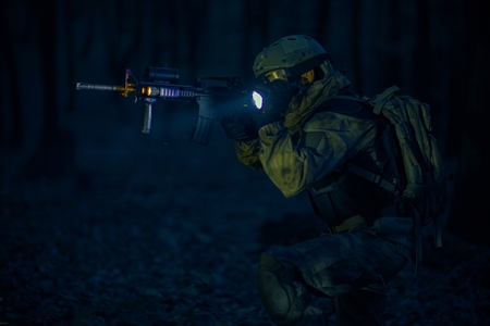 Military Night Operation. Soldier with Assault Rifle and Flashlights at Night. Imagens