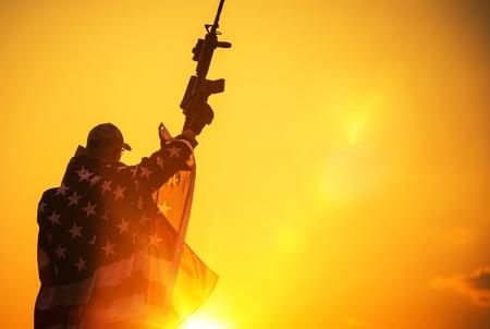 La victoria americana. Tropa del Ejército con el Rifle de Asalto cubierto por la bandera americana. American Patriot Foto de archivo