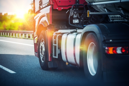 Red Semi Truck Speeding on a Highway. Tractor Closeup. Transportation and Logistics Theme. Stock Photo