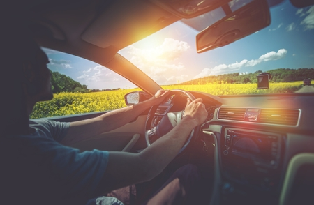여름 자동차 여행. 화창한 날에 유채 필드 사이에 운전 편안한 남자입니다. 자동차 운전.