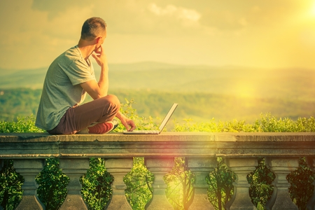 the place is outdoor: Creative Outdoor Works. Creative Entrepreneur with Laptop Working at His Favorite Outdoor Place with Scenic Panoramic View.