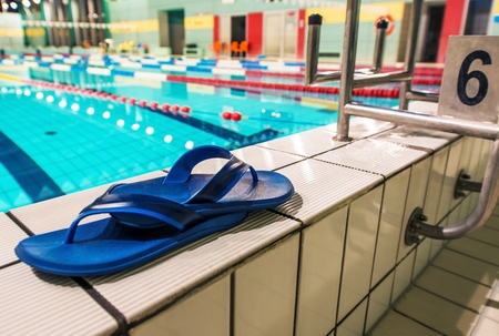 swimming shoes: Swimming Pool Shoes on the Edge of the Pool. Swimming Concept Photo.