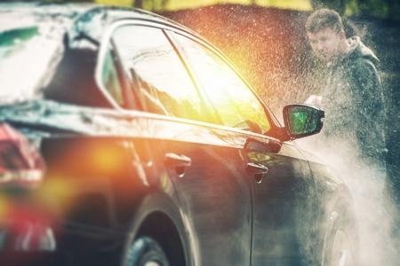 autolavado: Lavado de coches y limpieza. Los hombres de raza blanca joven que lava su coche. Foto de archivo