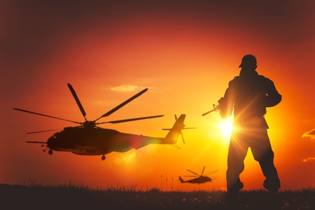 Military Mission at Sunset. Marines Helicopters Air Mission. Soldier with Assault Rifle Cover the Area.