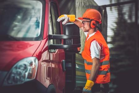 trabajando duro: Trabajador y su camión. El uso de hombres duros de trabajo de construcción Accesorios de seguridad.