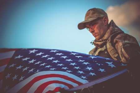 Young Army Veteran with American Flag Closeup Photo. Army Trooper with USA Flag. 스톡 콘텐츠