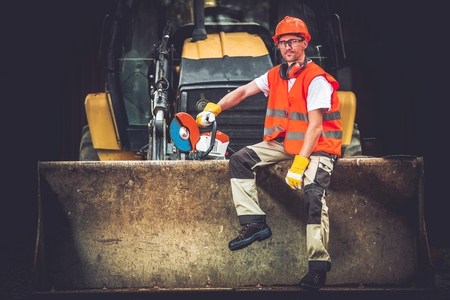 workless: Bulldozer Works Concept. Young Caucasian Men Seating and Relaxing on Bulldozer Blade. Happy Construction Worker. Ground Works. Stock Photo