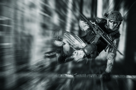 army men: Army Soldier in Action Jumping Over Fallen Tree. Military Concept.