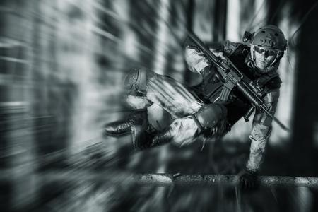 soldado: Soldado en acción salta sobre Árbol caído. Concepto militar.