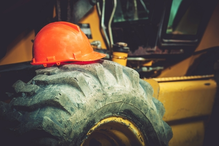 heavy duty: Work Safety Concept. Safety While Construction Working. Orange Safety Construction Helmet on  Large Heavy Duty Tractor Tire.