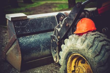 Construction Safety Helmet on Bulldozer Tire. Heavy Equipment Operation Safety.