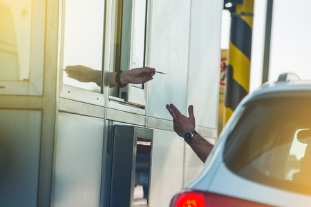 toll: Paying Highway Toll. Men in the Car Paying the Toll. Highway Systems. Stock Photo