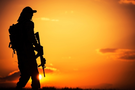 on duty: Call of Duty. Military Concept with Soldier with Assault Rifle on Duty During Sunset.