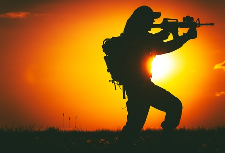 trooper: Army Trooper with Assault Rifle in Mission. Military Mission at Sunset. Military Concept.