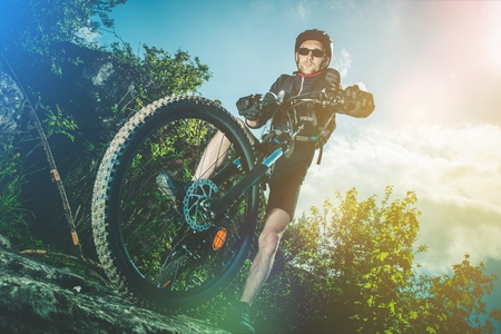 racing bicycle: Extreme Bike Ride Sport. Caucasian Biker on His Mountain Bike Riding on the Rocks. Stock Photo