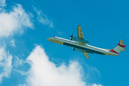 turboprop: Turboprop Jet Airplane Traveling. Airplane on the Cloudy Blue Sky.