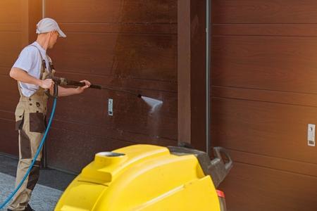 높은하여 차고 문 세제 물 압력을 가했다. 백인 남성 청소 차고 문.