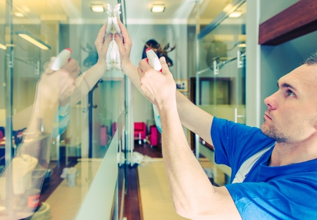 Glassy Office Interior Cleaning. Caucasian Men Cleaning Glass Elements. Stock Photo