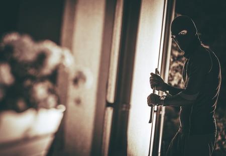 집에 침입하는 마스크에 집에 도둑. 하우스 도둑 개념 사진입니다. 스톡 콘텐츠