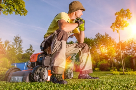 mowing grass: Garden is My Hobby and My Passion. Passionate Caucasian Men Watching His Beautiful Garden While Seating on His Grass Mower After Hard Working Day. Garden Lover.