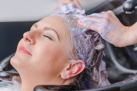 Hairdresser Making Hair Color For Female Client. Caucasian Woman Getting New Hair Color.