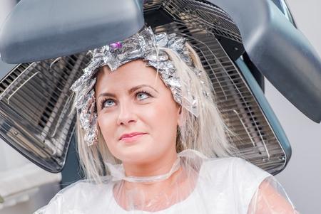 secador de pelo: Salón de belleza. La mujer caucásica Bajo Secador de pelo En espera de la siguiente paso de cortes de cabello.