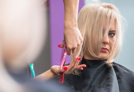 profesional: Blond Hair Woman Getting Hair Cut in the Beauty Salon.