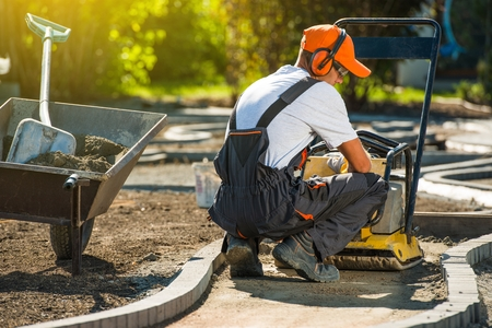 compactor: Plate Compactor Brick Works. Professional Brick Paver and His Plate Compactor at Work. Stock Photo