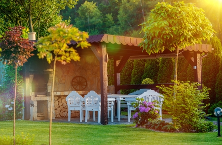 outdoor fireplace: Outdoor Garden BBQ Area. Garden Grilling Place with Fireplace and White Garden Furnitures. Stock Photo