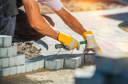 Professional 벽돌 작업자에 의해 정원 벽돌 통로 포장. 스톡 콘텐츠
