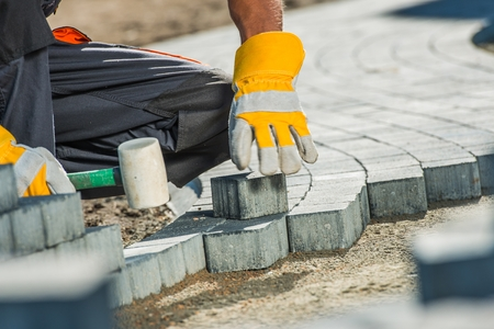 Brock Paving Closeup Photo. Construction Worker Paving Brick Pathway. Stock Photo