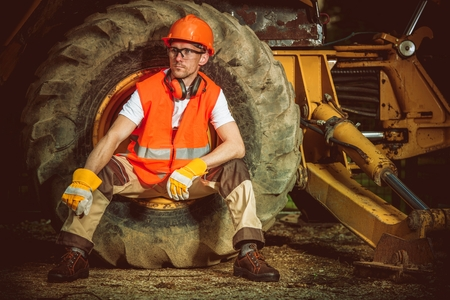 Caucasian Construction Worker While Seating Inside Large Dozer Wheel. Construction Site Concept.