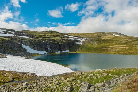 geology: High Mountain Landscape. Norway Mountains Scenery with Lake, Snow Spots and the Waterfall. Norway Geology.