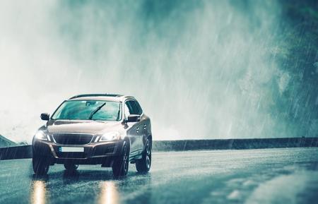 Řidičské auto v hustém dešti. Moderní kompaktní SUV Car Urychlení na mokré vozovce. Reklamní fotografie