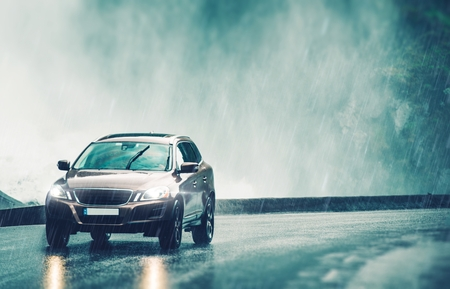 Driving Car in Heavy Rain. Modern Compact SUV Car Speeding on the Wet Road.