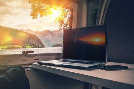 여행하는 동안 작업. 경치 피 요 르 드보기와 야영 테이블에 노트북 컴퓨터. 캠핑 동안 RV에서 작업 컴퓨터.