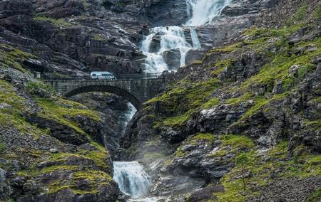 motorcoach: Norway Camper Van Trip. Trollstigen Bridge, Stigfossen Falls and Serpentine Mountain Road in Rauma Municipality, Norway. Motorhome on the Scenic Waterfall Bridge.