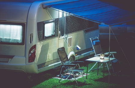 Travel Trailer Camping Romantic Setup. Modern Travel Trailer and Camping Furnitures Under the Awning. Modern Caravaning. Archivio Fotografico
