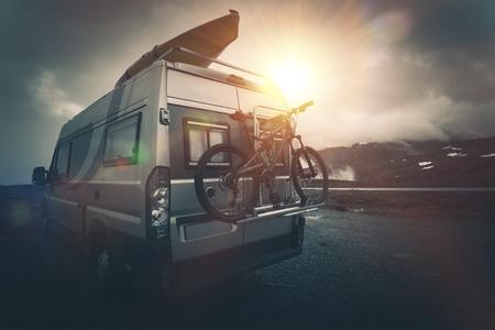 궁극적 인 야영 자 캠핑. 자전거 선반에 자전거와 캠핑카 지붕에 카약으로 현대 캠핑. Boondocking 야영. 스톡 콘텐츠
