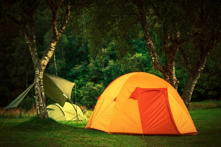 campground: Small Orange Tent Camping. Wilderness Camping Theme. Campground Place. Stock Photo