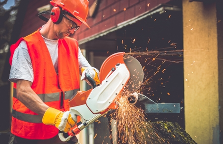 construction workers: Construction Worker with Metal Cutter While Cutting Metal Pipe. Caucasian Worker.