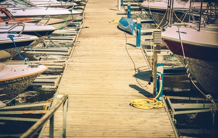 motorboats: Small Motorboats Marina with Straignht Wooden Deck Alley. Boating and Fishing Theme. Stock Photo