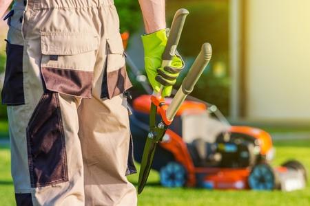 Landscaping professionale. Giardiniere Pro con forbici grandi e altre attrezzature da giardinaggio. Archivio Fotografico